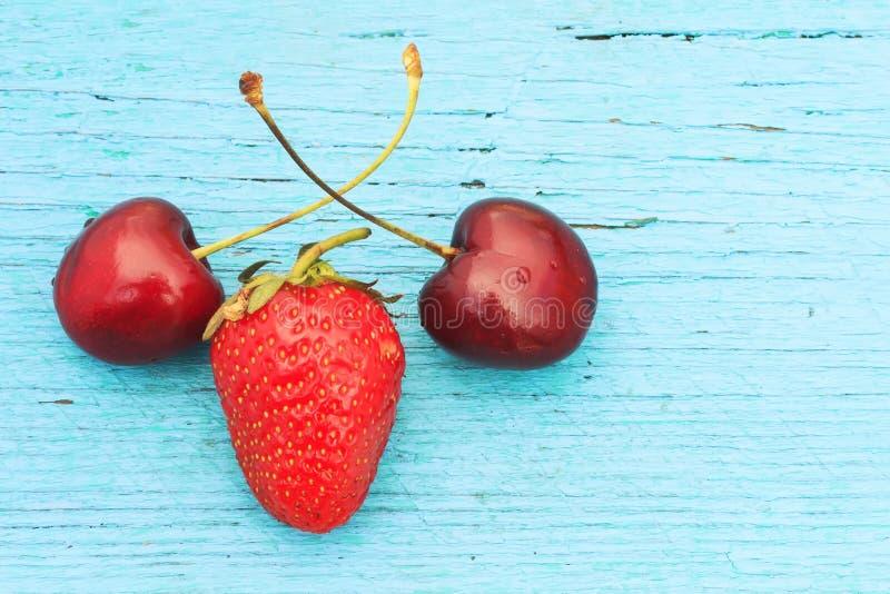 reife rote Kirschen und Erdbeeren, die auf einem blauen Holztisch liegen lizenzfreie stockfotografie