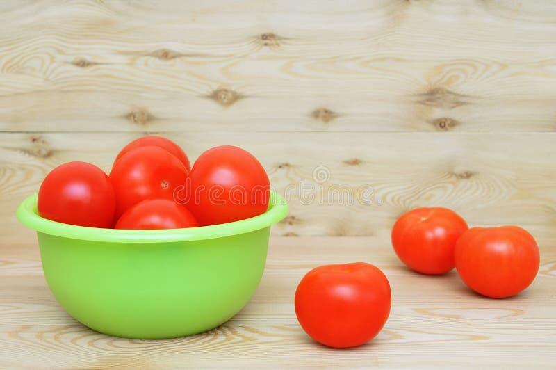 Reife rote Tomaten in einer grünen Schüssel auf Holzboden Ernte lizenzfreie stockfotos