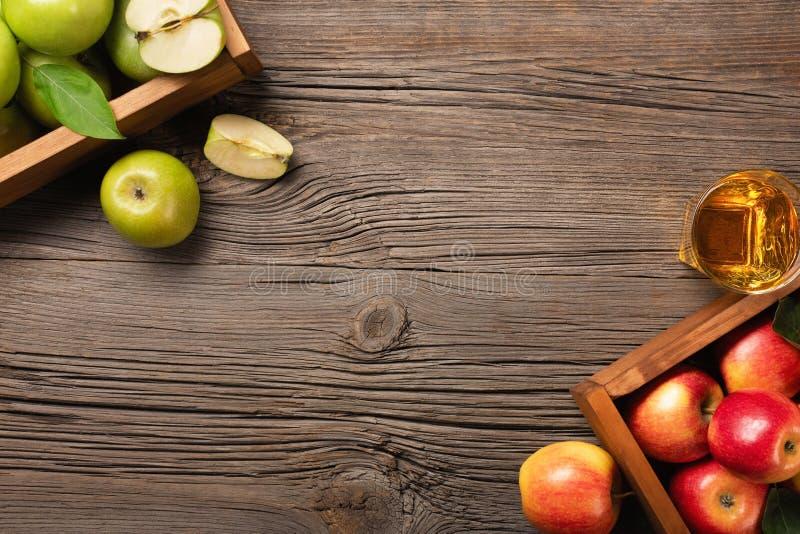 Reife rote und grüne Äpfel in der Holzkiste auf einem Holztisch stockfotografie