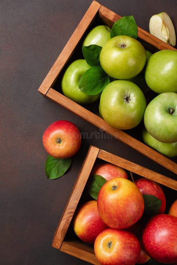 Reife rote und grüne Äpfel in der Holzkiste auf einem rostigen Hintergrund lizenzfreie stockfotos