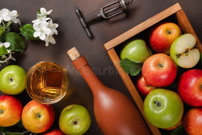 Reife rote und grüne Äpfel in der Holzkiste mit Niederlassung von weißen Blumen, von Glas und von Flasche Apfelwein auf einem ros stockbild