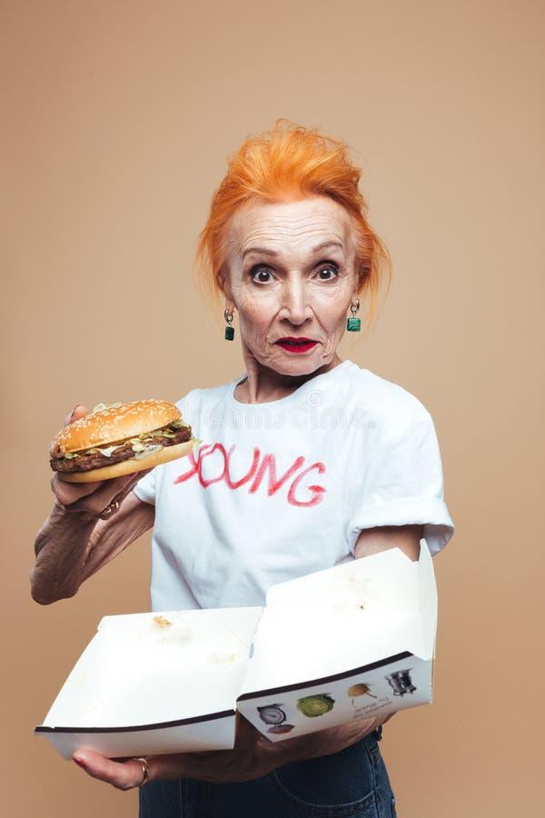 Download Reife Rothaarigemodefrau, Die Burger Isst Schauen Der Kamera Stockbild - Bild von alter, augen: 96933897