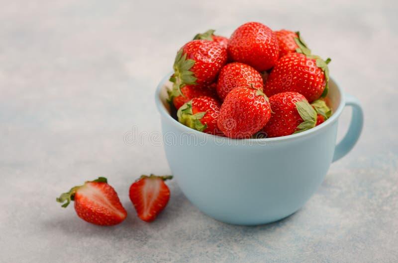 Reife süße Erdbeeren in der blauen Schale auf blauem konkretem Hintergrund stockbilder