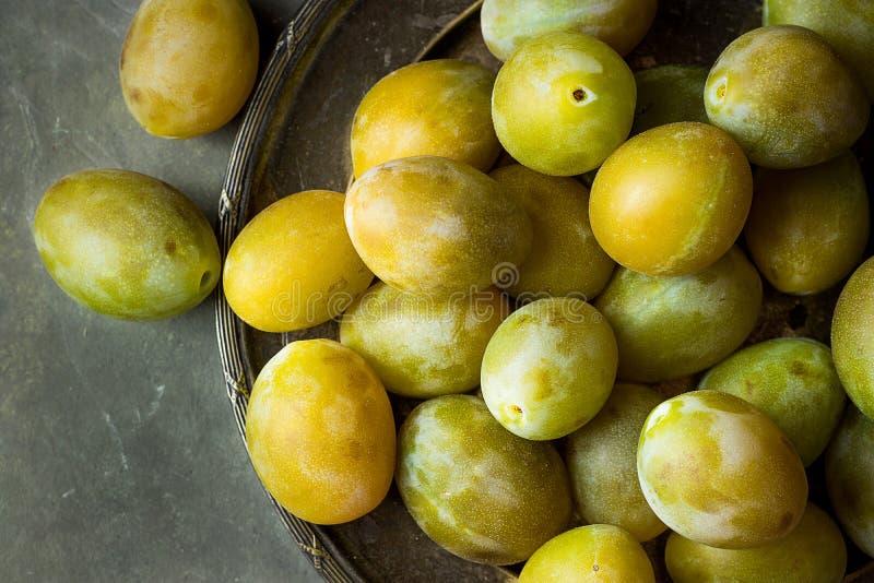 Reife saftige bunte gelbe und grüne Pflaumen auf Weinlesemetallteller Dunkler Steinhintergrund Herbst lizenzfreies stockfoto