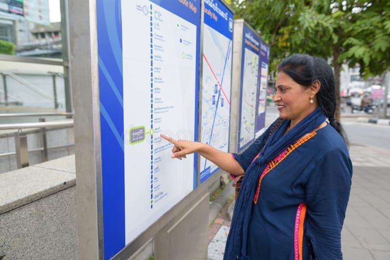 Reife schöne indische Frau, die draußen Zugkarte betrachtet stockfotos