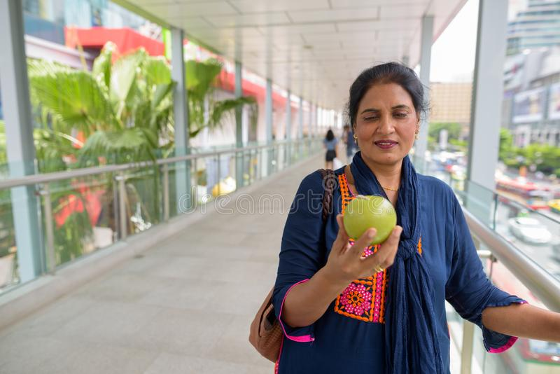 Reife schöne indische Frau, die grüne Apfelfrucht hält lizenzfreie stockfotos