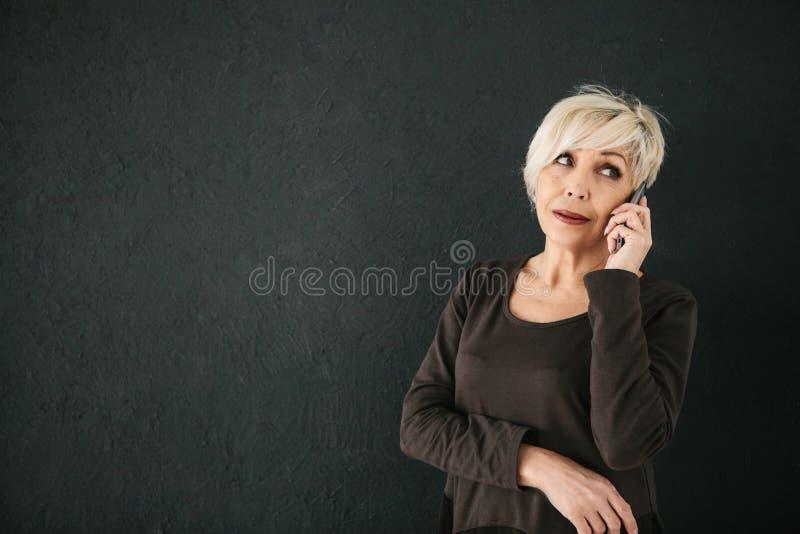 Reife schöne positive Frau, die am Handy spricht stockbilder