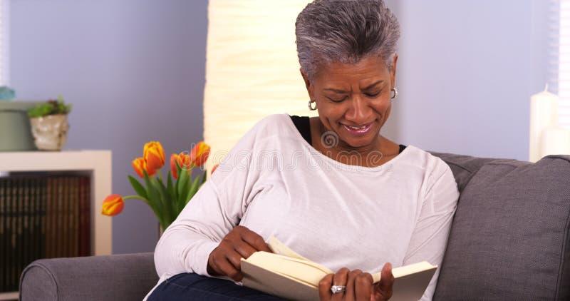 Reife schwarze Frau, die ein gutes Buch genießt lizenzfreie stockbilder