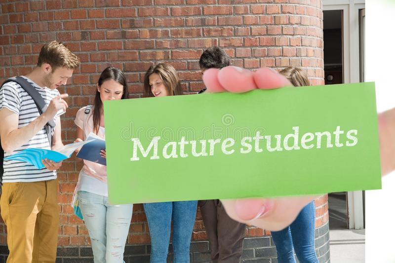 Reife Studenten gegen die glücklichen stehenden und lesenden Studenten lizenzfreie stockbilder