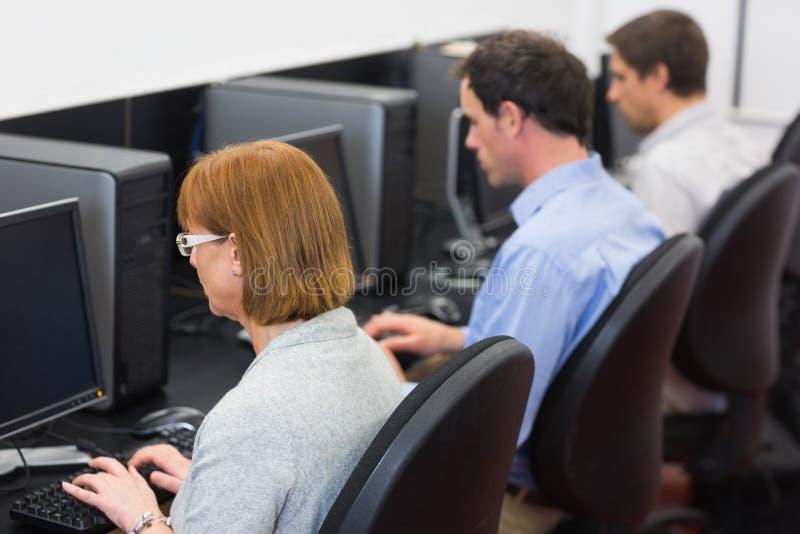 Reife Studenten im Computerraum stockbilder
