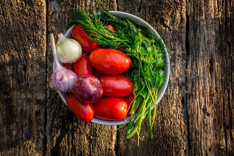 Reife Tomaten in der Schüssel auf hölzernem Hintergrund lizenzfreie stockfotografie