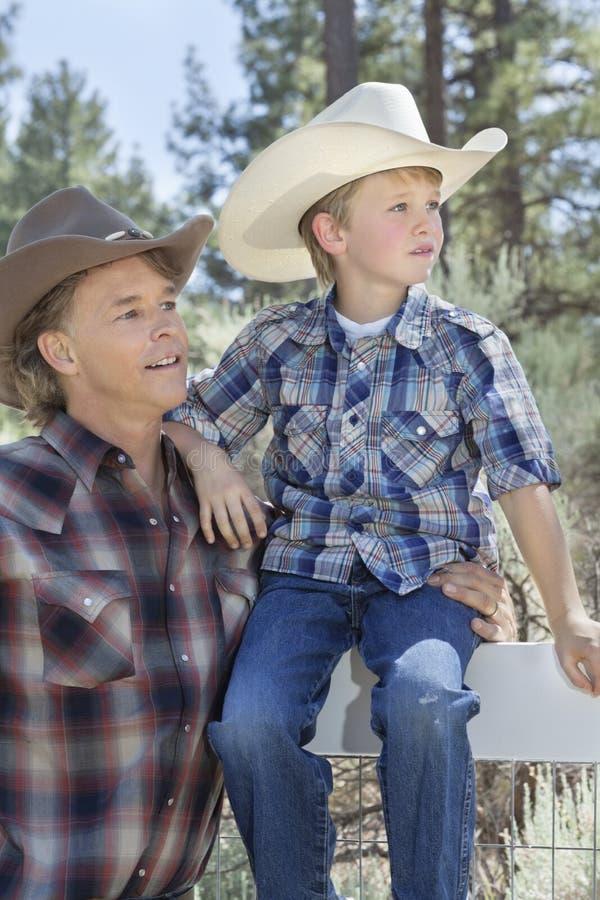 Reife tragende Cowboyhüte des Vaters und des Sohns, die weg im Park schauen stockfotos