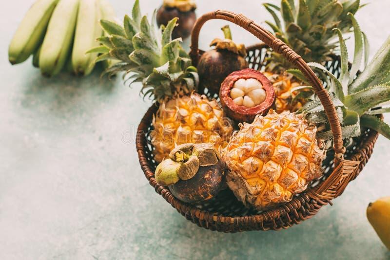 Reife tropische Früchte in einem Korb, Ananas, Mangostanfrucht lizenzfreies stockfoto
