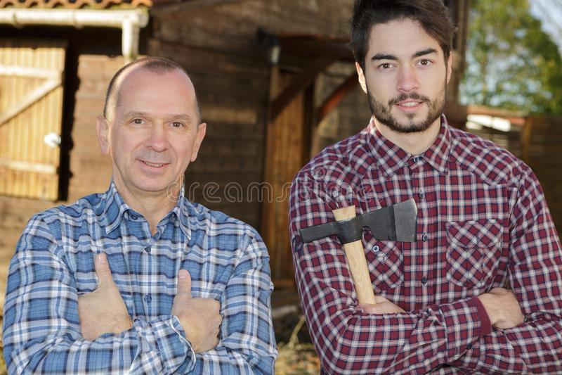 Reife und junge Männer, die nahe der hölzernen Hütte hält Axt aufwerfen stockfoto