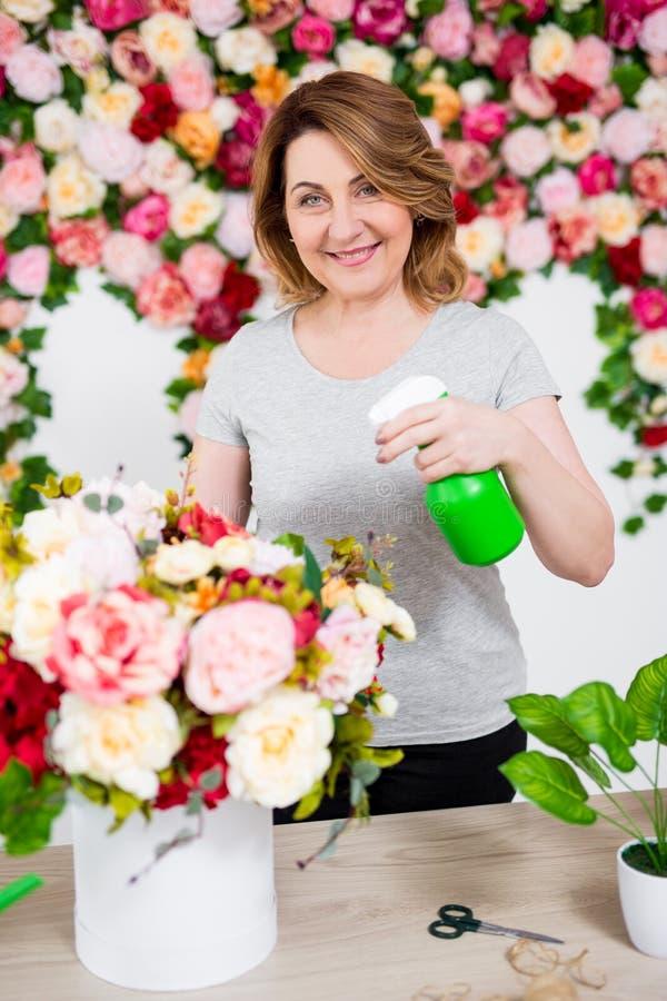 Reife weibliche Bewässerungsblumen des Floristen oder des Gärtners mit Sprühflasche im Blumenladen stockbild