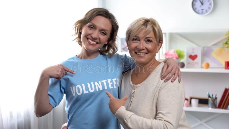 Reife weibliche und junge Frau, die auf freiwillige Aufschrift auf T-Shirt zeigt stockbild