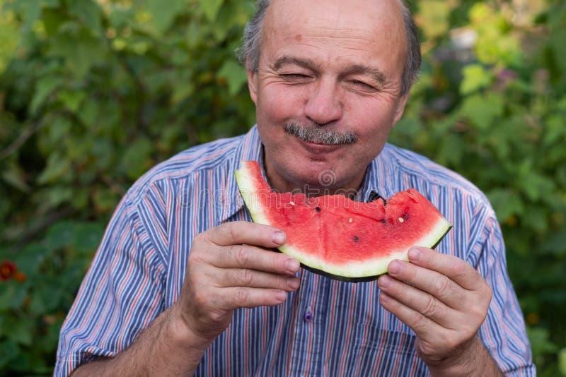 Reifen Sie den kaukasischen Mann mit dem Schnurrbart saftige Wassermelone mit Vergnügen und dem Lächeln essend lizenzfreie stockfotos