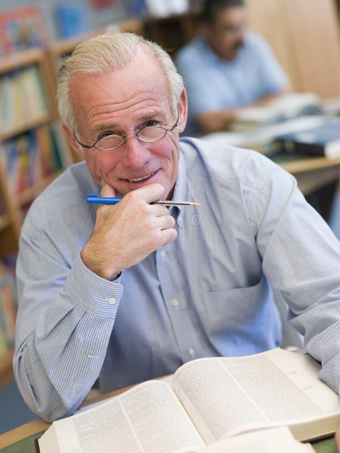 Reifen Sie den männlichen Kursteilnehmer, der in der Bibliothek studiert stockbilder