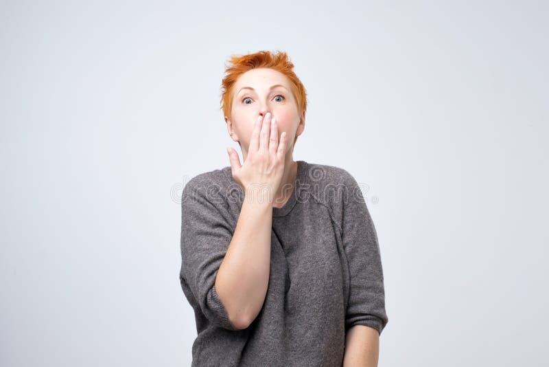 Reifen Sie die überraschte Frau, die ihren Mund mit der Hand auf grauem Hintergrund bedeckt Ich sage nicht diesem Geheimnis jedem lizenzfreie stockfotos