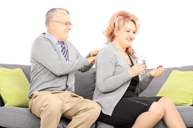 Reifen Sie, die Pillen und Ehemann nehmend, die ihr eine Rückenmassage geben lizenzfreies stockbild