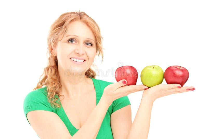 Reifen Sie die schöne Frau, die drei Äpfel sitzt und anhält lizenzfreie stockbilder