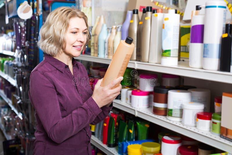 Reifen Sie kaufendes Volumenshampoo des weiblichen Kunden im Supermarkthaar lizenzfreies stockfoto