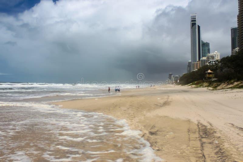 Reifenbahnen und unidentifizierbare Touristen auf Strand watend heraus in Brandung am stürmischen Tag mit dunklen Wolken bei Gold stockfotos
