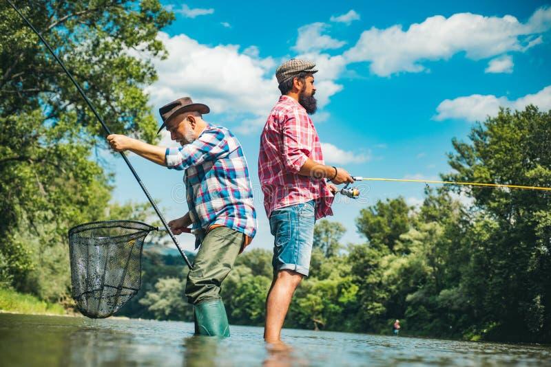 Reifender Mann mit Freund Angeln Bärenfischer in Wasser Mit Inspiration machen Bärenfischer Mature man lizenzfreie stockfotos