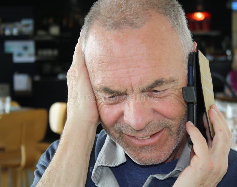 Reifer älterer Mann, der an einem Handy spricht lizenzfreie stockfotos