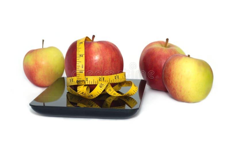 Reifer Apfel, Küchenskalen und messendes Band lokalisierten Nahaufnahme lizenzfreie stockfotografie