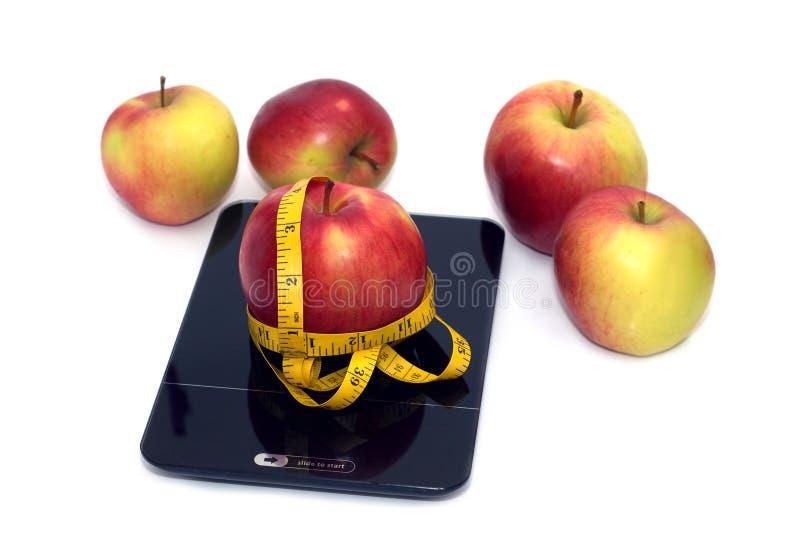 Reifer Apfel, Küchenskalen und messendes Band lokalisierten Nahaufnahme lizenzfreies stockbild
