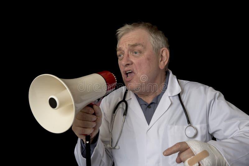 Reifer Doktor, der in ein Megaphon protestiert und schreit stockbild