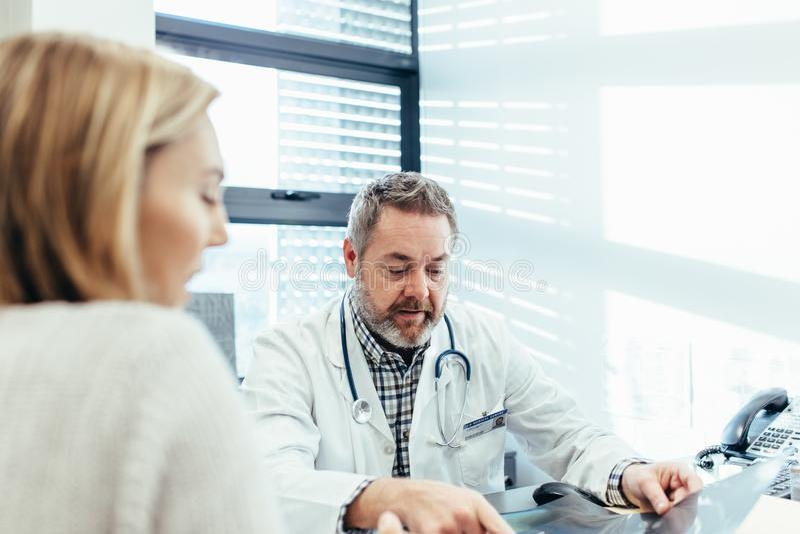 Reifer Doktor, der mit weiblichem Patienten in der Klinik spricht lizenzfreies stockfoto