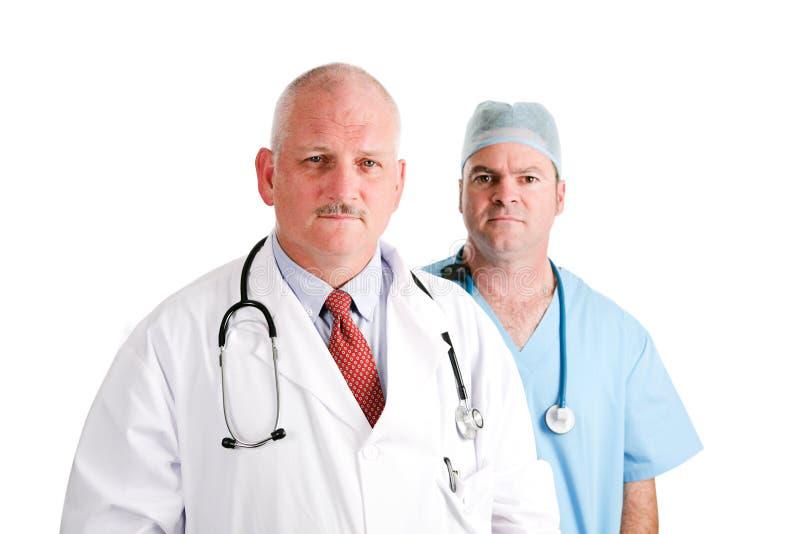Reifer Doktor und chirurgischer Internierter stockbild