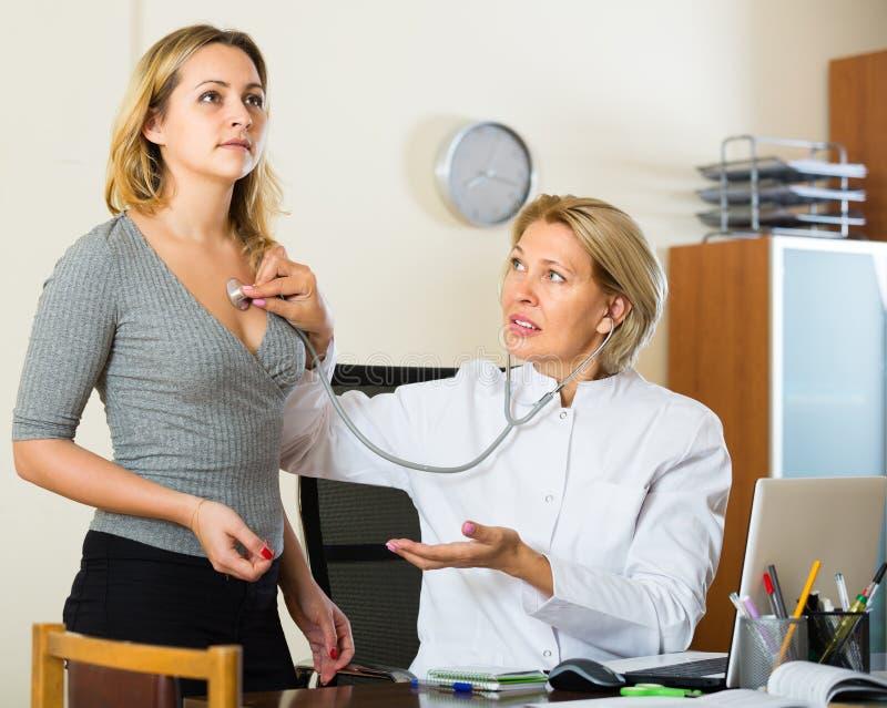Reifer Doktor und kranker Patient stockbild