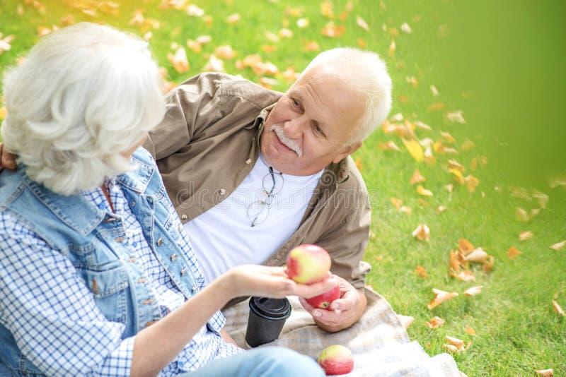Reifer Ehemann und Frau essen Früchte stockbilder