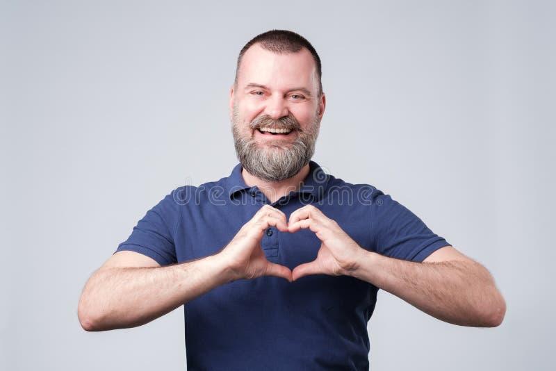 Reifer europäischer Mann mit dem Bart, der aus dem Handherzen heraus macht lizenzfreie stockbilder