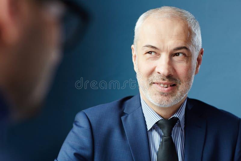 Reifer Geschäftsmann bei der Sitzung stockfoto
