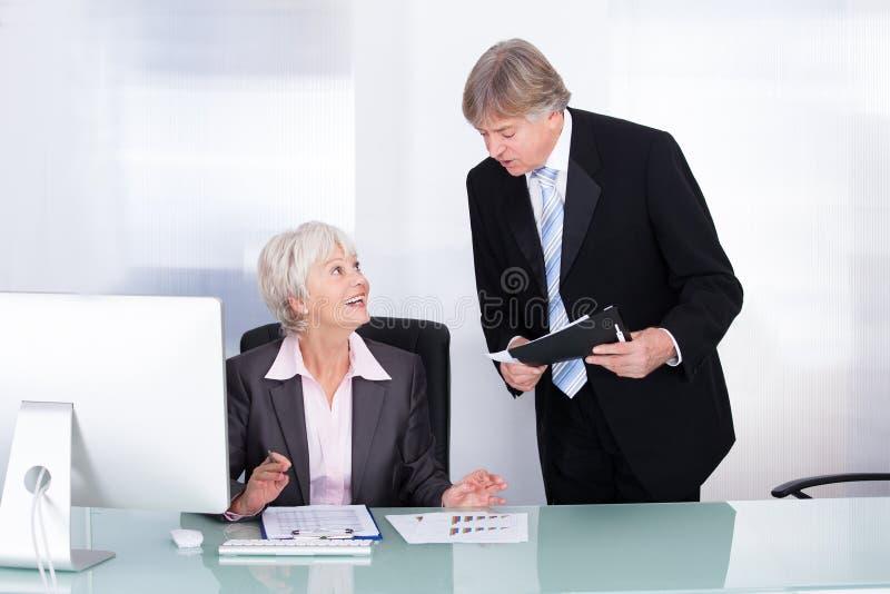 Reifer Geschäftsmann-And Businesswoman At-Arbeitsplatz stockfotografie