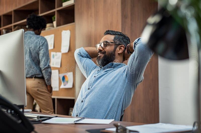 Reifer Geschäftsmann, der bei der Arbeit sich entspannt stockfotografie