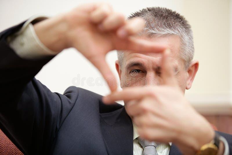 Reifer Geschäftsmann, der durch den quadratischen Rahmen macht durch Finger schaut stockbild