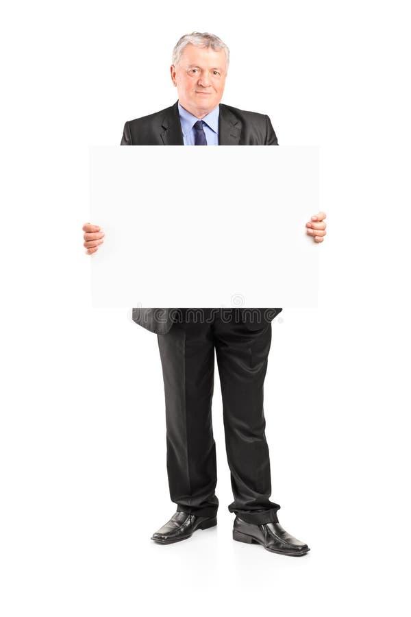 Reifer Geschäftsmann, der ein leeres Plakat hält lizenzfreie stockfotos