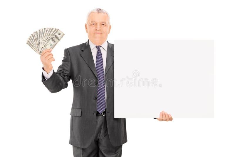 Reifer Geschäftsmann, der Geld und leere Fahne hält stockfotos