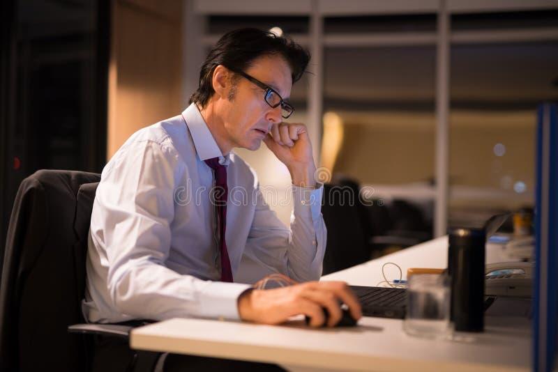 Reifer Geschäftsmann, der im Büro nachts sitzt und arbeitet stockfotografie