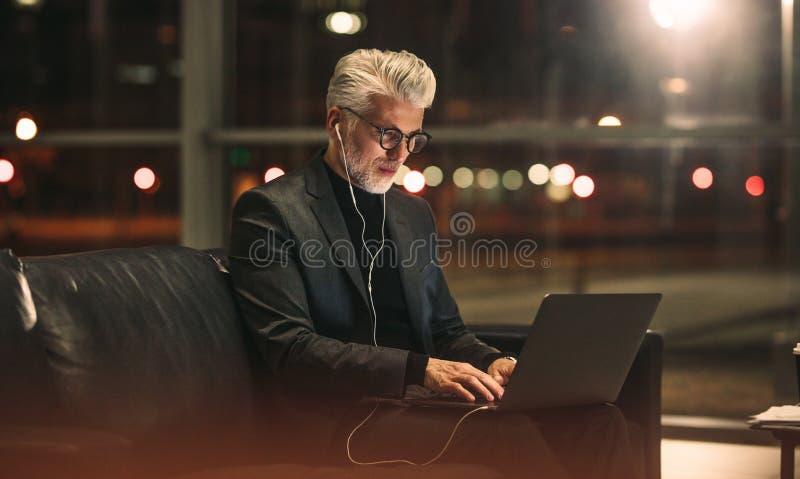 Reifer Geschäftsmann, der an Laptop im Büro arbeitet stockbild