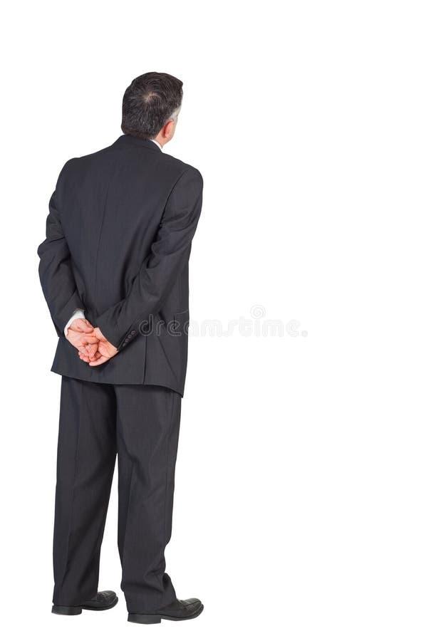 Reifer Geschäftsmann, der mit den Händen hinten zurück steht stockfotografie