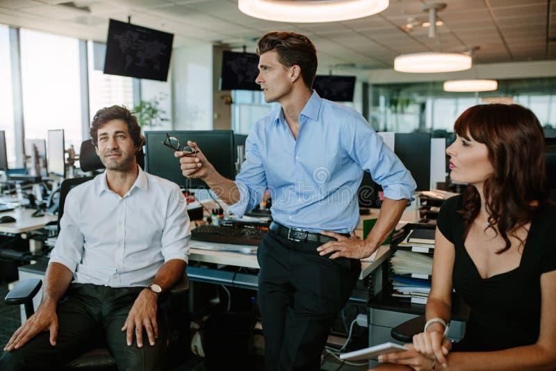 Reifer Geschäftsmann, der neue Pläne mit Kollegen bespricht lizenzfreie stockbilder