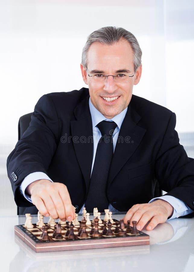 Reifer Geschäftsmann, der Schach spielt lizenzfreie stockbilder