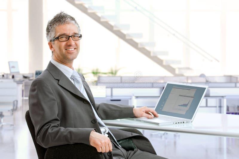 Reifer Geschäftsmann, der am Schreibtisch sitzt lizenzfreie stockfotos