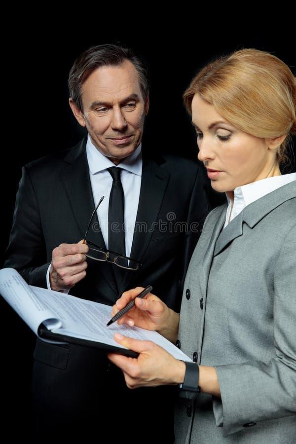 Reifer Geschäftsmann, der unterzeichnende Papiere der blonden Geschäftsfrau betrachtet lizenzfreie stockfotos
